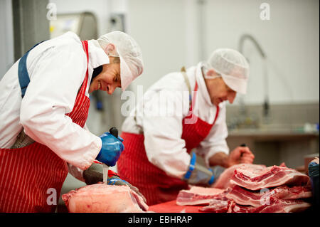 Las carnicerías en el trabajo en una fábrica procesadora de carne Foto de stock