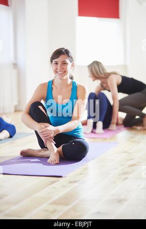 Retrato de mujer joven sentada en el suelo en clase de pilates
