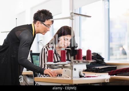 Dos costureras, mirando hacia la máquina de coser en el taller