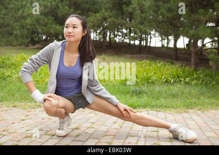 Los jóvenes corredoras estirar las piernas en la posición de estacionamiento