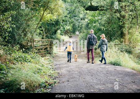 Padre y dos niñas paseando a un perro en la carretera rural
