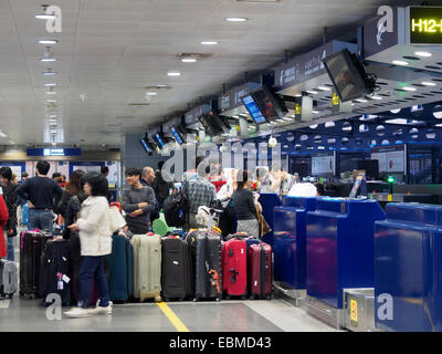 Pasajeros con equipaje esperando en línea en el mostrador de la recepción en el Aeropuerto Internacional de Pekín, China