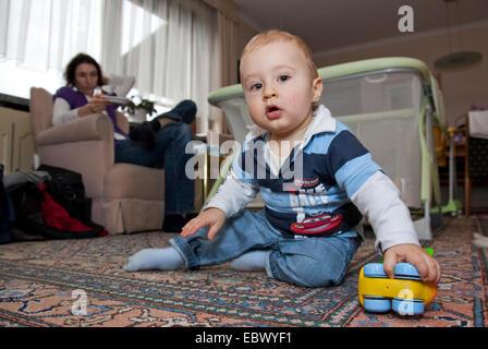 Chico jugando en el piso, su madre sentada en un sofá mantener un ojo sobre él