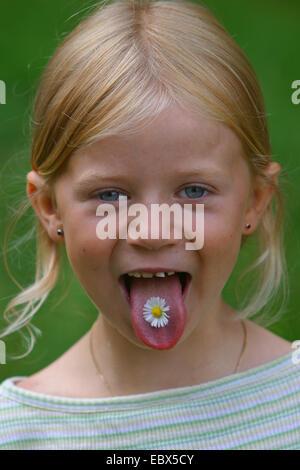 Daisy común, césped, Margarita (Bellis perennis margarita en inglés), una chica con una flor en su lengua, Alemania