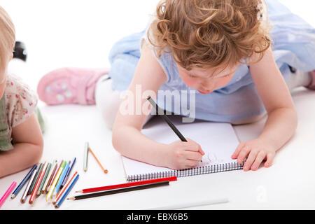 Las niñas tirados en el groud de dibujo con lápices