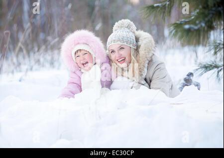 Feliz de la madre y el niño acostado en la nieve outdoor Foto de stock