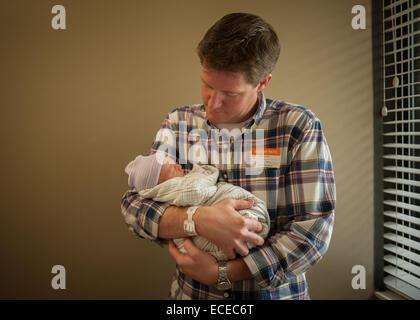 Padre sosteniendo bebé recién nacido en el hospital