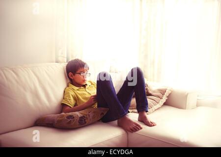 Mestizos chico leyendo libro sobre el sofá de la sala