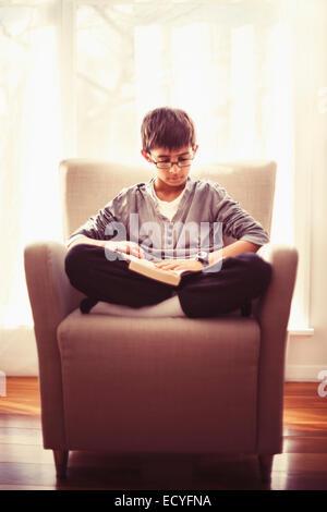 Mestizos boy libro de lectura en el sillón