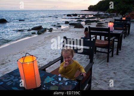 Chica sentada sola en un restaurante de la playa en Sihanoukville. Al anochecer se convierte en el lugar de encuentro para saborear una buena cerveza. Sihanoukvill