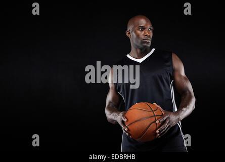Imagen del monte joven atleta Afro Americana sosteniendo una pelota de baloncesto mirando a otro lado con espacio de copia. Musculoso jugador de baloncesto.