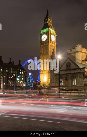 Las casas del parlamento, el Big Ben y el London Eye de noche con rayas de tráfico. Foto de stock