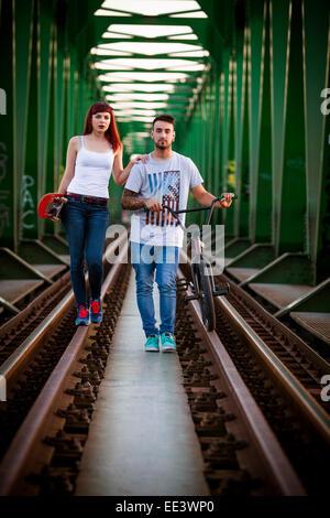 Pareja joven con bicicleta BMX caminando por el puente