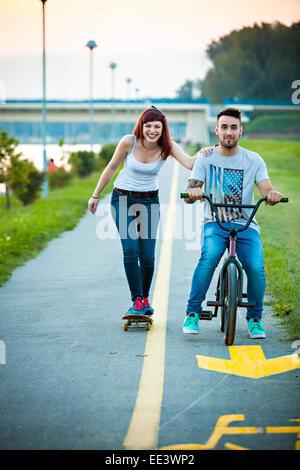 Pareja joven con bicicleta BMX y skate al aire libre