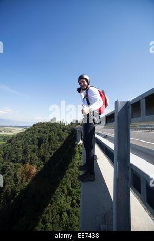 Este hombre va a saltar desde el puente. Parece que está muy emocionada de hacer este salto BASE y así él sonríe mucho.