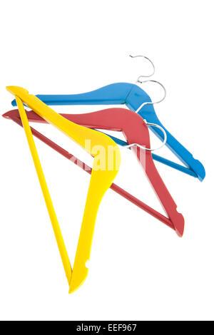 Colorido perchas de ropa en amarillo, rojo y azul aislado sobre fondo blanco.