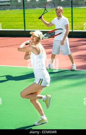 Matrimonio joven jugando al tenis en blanco sportwear en la cancha de tenis al aire libre en verano Foto de stock