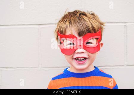 Retrato de un niño sonriente con máscara de superhéroe