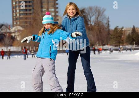 Madre de la enseñanza hija patinar en el hielo al aire libre