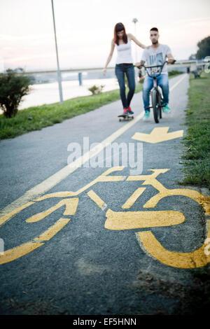 Pareja joven con skate y bicicletas BMX afuera