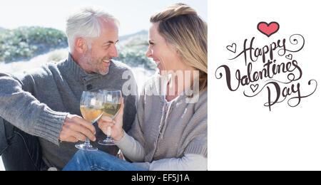 Imagen compuesta de la pareja disfrutando de vino blanco en un picnic en la playa. Foto de stock