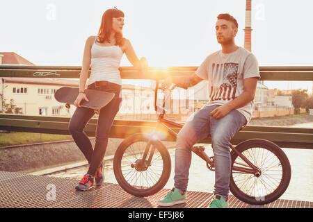 Pareja joven con skate y bicicletas BMX descansando en el puente