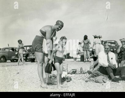 Diciembre 12, 2014 - Canadá - circa 1930: Reproducción de una antigua foto muestra a una mujer en un traje de baño y una tapa de goma pone una niña en la playa, viéndolos ancianos empresario en un empate, sin chaqueta, que está junto a la arena. En el fondo, una mujer en un traje de baño y un traje y sombrero contra el telón de fondo de automóviles. (Crédito de la Imagen: © Igor Golovniov/Cable/ZUMAPRESS.com) Zuma.