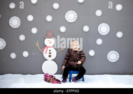 Niña con copo de nieve y el muñeco de nieve recortes. Foto de stock
