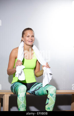 Mujer joven sentado en un banco tomando un descanso en el gimnasio Foto de stock