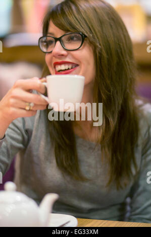 Hermosa joven disfrutando de una bebida caliente con amigos en un acogedor café.