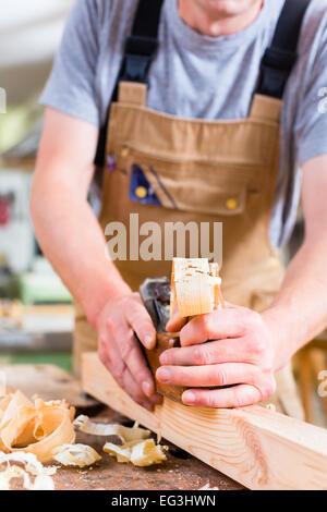 Carpenter trabaja con un cepillo para madera sobre la pieza en su taller de carpintería o