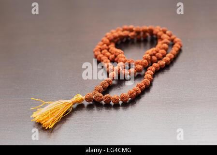 Japa mala en la mesa. Rosarios elaborados a partir de las semillas del árbol rudraksha
