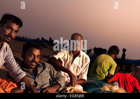 Los pescadores indios relajarse al final del día en la playa de Cherai en el sur de la India.