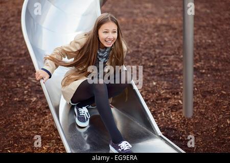 Feliz adolescente que se está desdichando en un tobogán en un patio de recreo