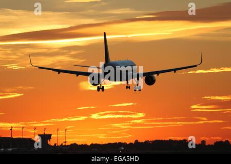 Un avión que aterrice en un aeropuerto durante la puesta de sol en vacaciones cuando viaje
