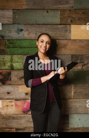 Retrato de mujeres jóvenes y atractivas con un ejecutivo portapapeles de pie contra una pared de madera en la oficina. Los jóvenes afroamericanos