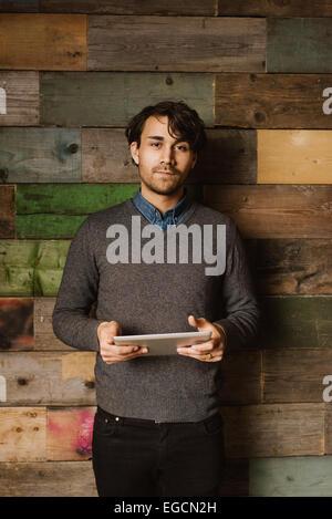 Retrato de un joven confiado sosteniendo una tableta digital mirando a la cámara. Ejecutivo con Tablet PC.
