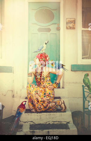 Mujer joven posando en las escaleras con loros
