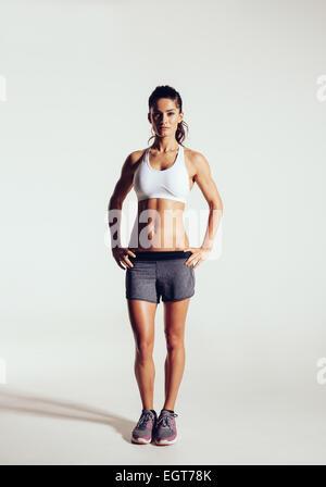 Mujer joven con hermoso cuerpo sano slim posando en el estudio. Fitness modelo femenino en ropa deportiva sobre fondo gris