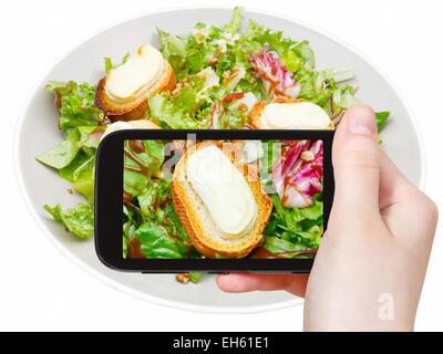 Fotografiar comida concepto - toma de fotografía turística de ensalada verde con queso de cabra en gadget móvil, Italia