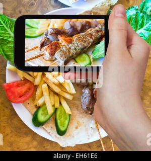 Fotografiar comida concepto - toma de fotografía turística de pinchos mezcla árabe kebabs en gadget móvil, Jordania