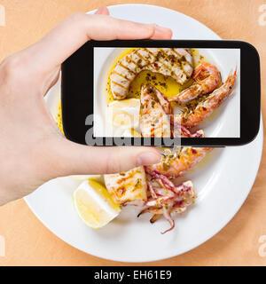 Fotografiar comida concepto - toma de fotografía turística sicilianos pescado asado mix en placa blanca en gadget móvil, Sicilia, Italia