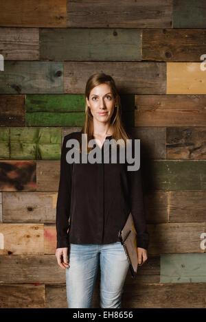 Retrato de la hermosa joven empresaria de pie contra una pared de madera mirando a la cámara. Mujer caucásica en casuals en Office