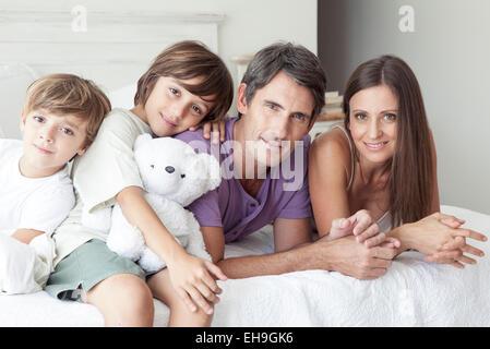 Padres e hijos jóvenes relajándose juntos en la cama, Retrato