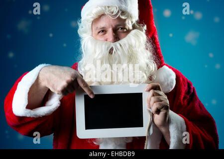 Retrato de la imagen de Santa Claus en chaqueta roja con nieve señalando con el dedo sobre una pizarra en blanco
