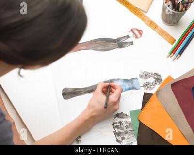 Vista superior del diseñador de moda sentados frente al escritorio, bosquejando en su atelier.