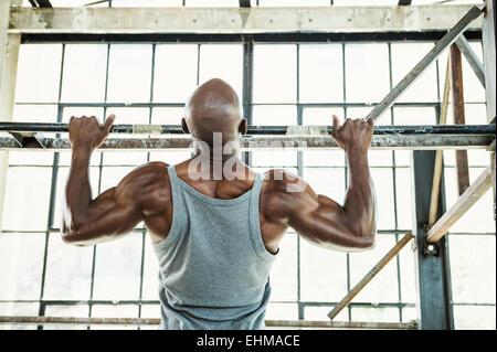 Hombre Negro haciendo pull-ups en el almacén