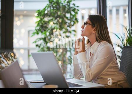 La empresaria caucásica pensando en escritorio de oficina Foto de stock