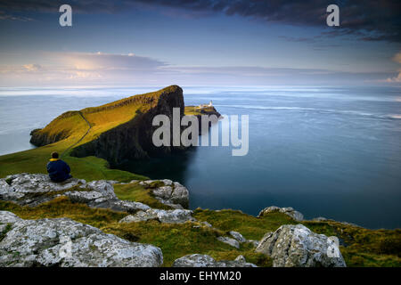Mitad hombre adulto sentado en una roca mirando al mar en Neist Point, Escocia