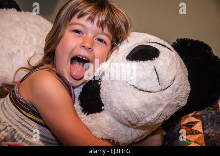 Cuatro años de edad, niña actuando por su lengua se pegue, abrazando su gran oso panda de peluche Foto de stock